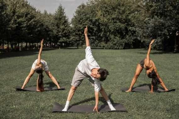 Teenagers practising yoga outside